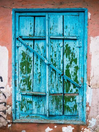 Old blue closed window with shutters. Ruined wall of an old house. Texture and Background Stock fotó