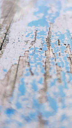 Selective focus shot of weathered blue paint wearing off some rotting wood.