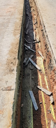 A trench showing a cross section of a road. Stock Photo