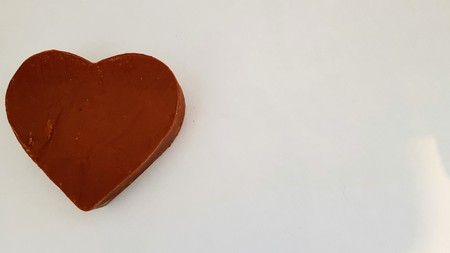 Thick, solid, milk chocolate heart on a light background. Stock Photo