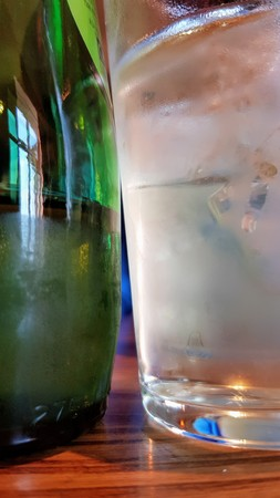 Close up of an ice cold green bottle of drink next to a frosted ice cold glass Stock Photo