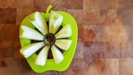 A green apple fully separated into chunks with the core removed by a green apple shaped slicer, divider and corer on a wooden butchers block..