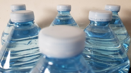 Plastic bottles focused on the middle row of caps. Stock Photo