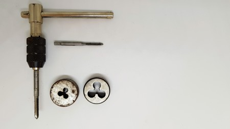 A tap and die set with two taps and two dies.