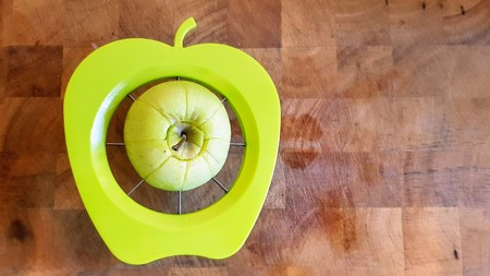 A green apple being separated into chunks by a green apple shaped slicer, divider and corer on a wooden butchers block.