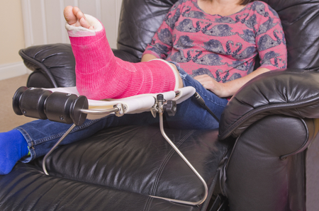 A lady with a fractured leg sat in an armchair with her pink pot on a raised leg support photo