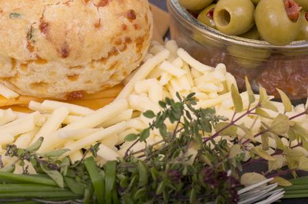 queso rallado: Queso y un bollo cebolleta con un plato de aceitunas rellenas sentaron en rebanadas de queso cheddar rojo queso rallado queso y un manojo de hierbas frescas