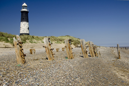 defenses: World War 2 Beach Defenses and Lighthouse Stock Photo