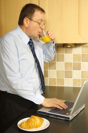 stood: A business man stood in a kitchen working at a laptop whilst eating breakfast
