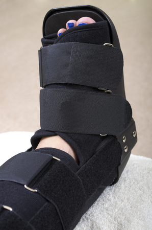 orthopaedic: A  lady with a fractured leg sat on a chair  with her leg supported in an orthopaedic boot, showing only her leg.