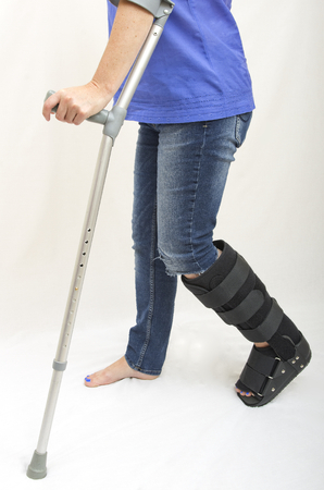 orthopaedic: A lady with a fractured leg in an orthopaedic boot walking with the aid of crutches Stock Photo