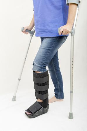 pierna rota: Una señora con una pierna fracturada en una bota ortopédica a caminar con la ayuda de muletas