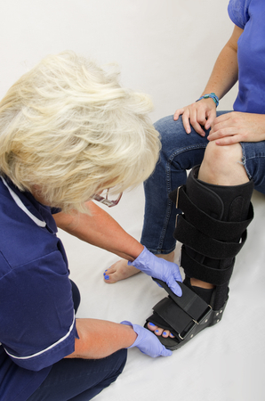 orthopaedic: Lady with a broken leg having an orthopaedic boot fitted by a nurse.