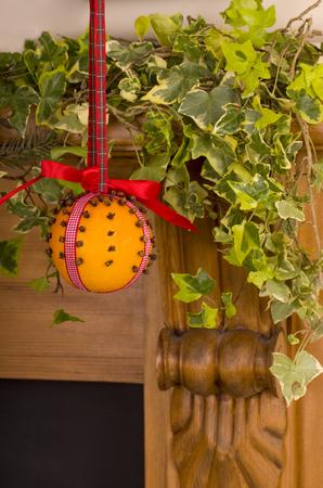 fire surround: Christingle Orange hanging on a Fire surround