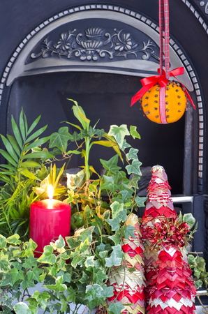 fire surround: A christmas fire side display with a Christingle decoration Stock Photo