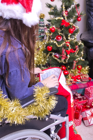 christmas stocking: Disabled girl in a wheelchair taking presents from a Christmas Stocking