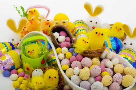 christian festival: A selection of Easter Eggs  and fluffy chicks on a porcelain ladle.