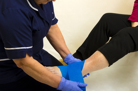 ankle strap: Senior lady with a nurse applying a support bandage to her damaged ankle