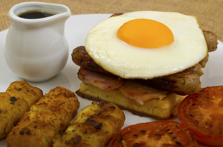 papas doradas: Breakfast of waffles, bacon, egg, sausage in a stack with tomato, hash browns and a jug of maple syrup