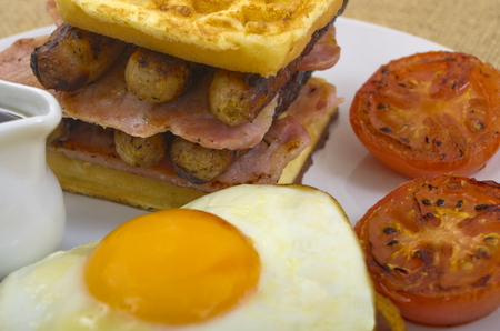 papas doradas: Breakfast of waffles, bacon, egg, sausage in a stack,  a side of tomato, and sunny side up egg sat on the hash browns with a jug of maple syrup Foto de archivo