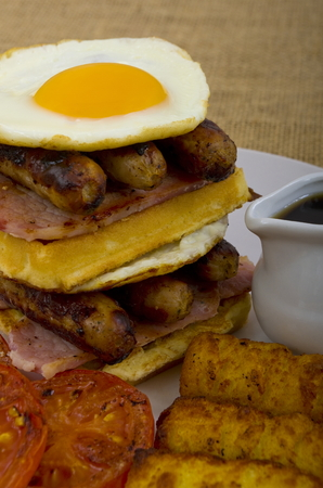papas doradas: Super size Breakfast of Double Waffle Stack Breakfast, waffles, bacon, eggs, sausage in a stack,  a side of tomato, and sunny side up eggs sat on with hash browns with a jug of maple syrup