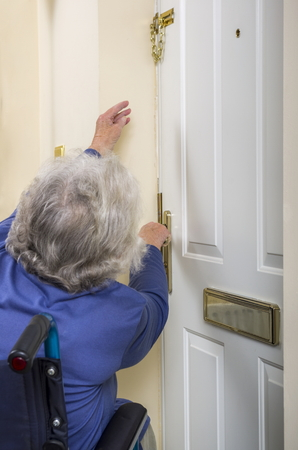 Disabled Senior Lady trying to open a door. Image of a senior disabled lady in a wheelchair trying to reach and take a safety chain off a door. Stok Fotoğraf