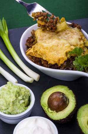 Cheesy Chilli Nachos with Guacamole. Cheesy Chilli Nachos served in a large spoon with sides of guacamole, Sour Cream, Avocados and Spring Onion. A quick St. Patrick's Day snack. Stock Photo