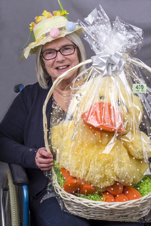 Easter Raffle Winner. Disabled lady in a wheelchair wearing an Easter Bonnet with a raffle prize of a large Easter Chick she has won. 스톡 콘텐츠