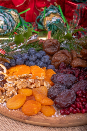 Platter of Festive Christmas Fruits. Wooden Platter loaded with a selection of fresh and dried Christmas Fruits.  Decorated with Holly, Cinnamon and Christmas parcels. Stock Photo