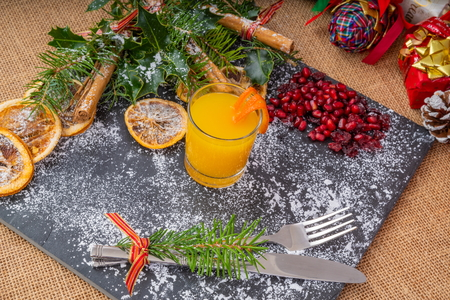 Christmas Slate Platter.  Decorated Slate Platter, with a glass of chilled fresh Orange Juice, ready for Festive food to be served.