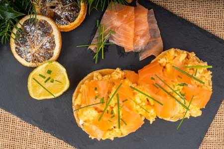 Festive breakfast of Smoked Salmon and Scrambled Egg on Pancakes, garnished with chives and lemon, served on a slate platter. Stock Photo
