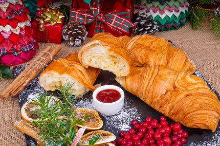 Christmas Continental Croissants Breakfast.  Festive breakfast of croissants and homemade strawberry jam served on a slate platter with a seasonal decoration and gifts. Фото со стока