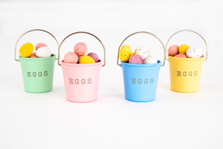 Four buckets filled with chocolate mini Easter Eggs on white background. Foto de archivo - 117101781