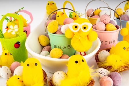 Easter chocolate mini eggs in buckets and a spoon with Easter Chicks. Foto de archivo - 117101785