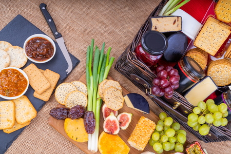 Wicker Hamper full of cheese, crackers with a selection of pickles and fruits.