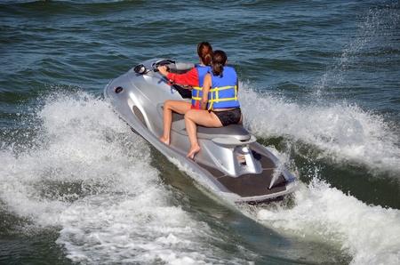 moto acuatica: Dos mujeres jóvenes de montar en tándem en un jet ski de plata de una actividad de fin de semana en todos los waterways.i sureste de la Florida Editorial