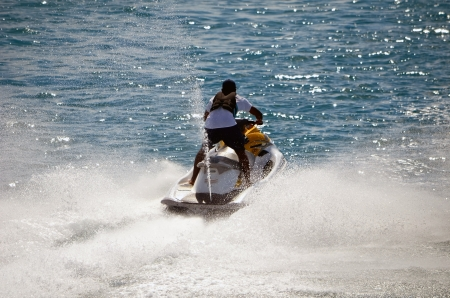 jet skier: Lone male jet skier racing along a channel in Nassau in the Bahamas