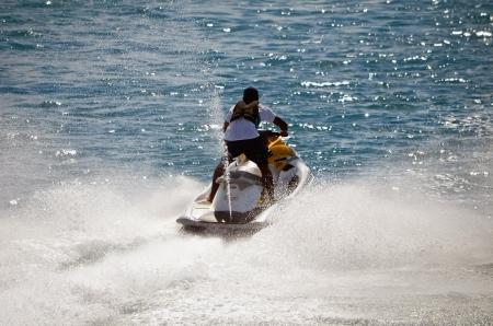 jet skier: Lone male jet skier racing along a channel in Nassau in the Bahamas
