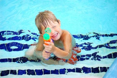Niño jugando con una pistola de agua en la parte menos profunda de la piscina condominio Foto de archivo - 18481818