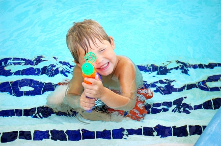 young boy playing with a water gun in the shallow end of a condo swimming pool