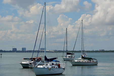 tuttle: Live aboard sailboats moored on the florida intra-coastal waterway near Miami Beach with a bridge on the Julia Tuttle Causeway linking miami beach and miami in the background.
