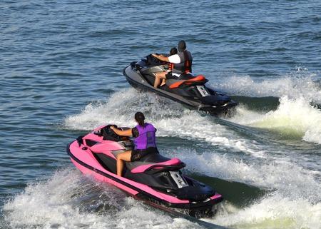 moto acuatica: Mujer joven que monta una moto de agua de color rosa y un joven acompañado por un niño en un jet ski negro disfrutando de un paseo familiar en el canal intra-costero florida cerca de la playa de Miami.