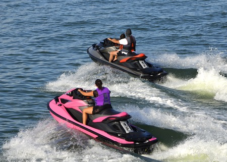 Young woman riding a pink jet ski and a young man accompanied by a child on a black jet ski enjoying a family outing on the florida intra-coastal waterway near miami beach.
