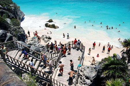 bathers: Wooden stairway winding down from cliffs overlooking a white sand beach in Tulum,Mexico a popular cruise ship tour destination . Editorial