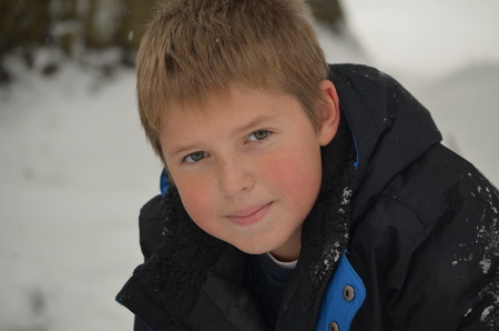 Portrait of a twelve year old boy  with freckles and rosy checks against a background of out of focus snow.