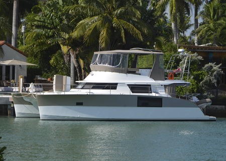 beach cruiser: Twin hulled cabin cruiser moored in an exclusive residential area of Miami Beach.
