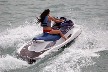 A young woman speeding across the florida intra-coastal waterway on a rented jet ski.