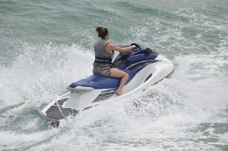 moto acuatica: Mujer joven que monta en un alquiler de jet ski en una actividad popular de vacaciones de primavera. Foto de archivo