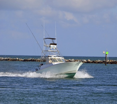 Sport fishing boat heading back to port through government cut in miamiflorida 免版税图像