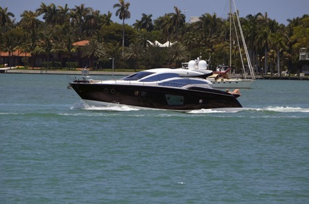 cruising: Sleek black motor yacht cruising the florida intracoastal waterway in the vicinity of miami beach Editorial